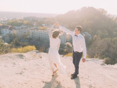 56755486 - portrait of smiling dancing wedding couple on the top of hill at city and sky background.